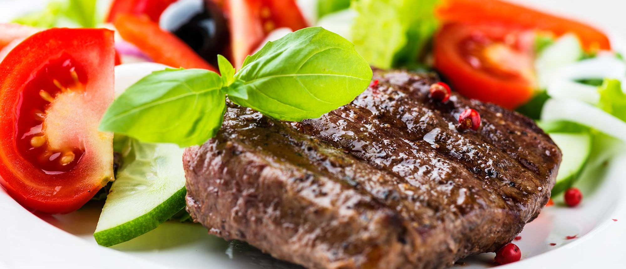 Closeup of grilled beef steak with fresh vegetables.